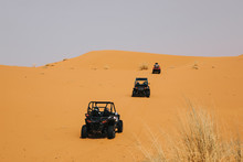 Off Road Buggies Crossing Dunes In The Desert. Rally Raid Adventure.