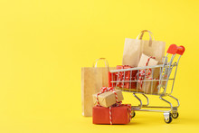 Shopping Cart Full Of Various Gift Boxes And Paper Bags.