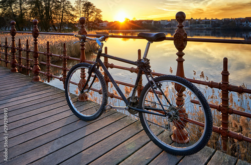 Aluminium Prints Bicycle Bicycle on a bridge with sunset in the background.