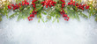 Leinwanddruck Bild Christmas or winter background with a border of green and frosted evergreen branches and red berries on a grey vintage board. Flat lay