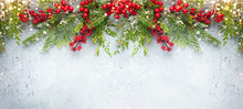 Christmas Or Winter Background With A Border Of Green And Frosted Evergreen Branches And Red Berries On A Grey Vintage Board. Flat Lay