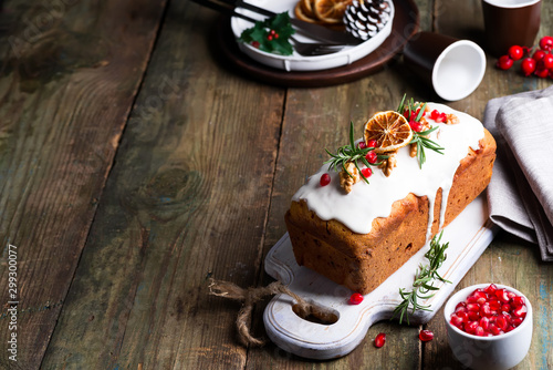 Montage in der Fensternische Brot Fruit cake dusted with icing, nuts, kernels pomegranate and dry orange on old wooden background. Christmas and Winter Holidays homemade cake