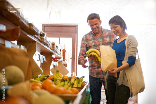 Mature Couple With Paper Bag Buying Fresh Bananas In Organic Farm Shop Together