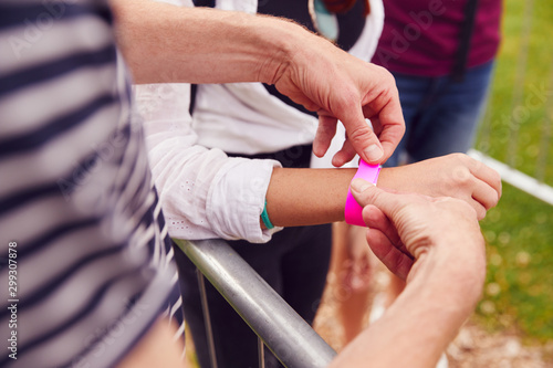 Close Up Of Friends At Entrance To Music Festival Putting On Security Wristbands - 299307878