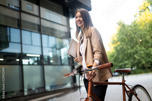 plakat Business woman with bicycle to work on urban street in city. Transport and healthy lifestyle concept