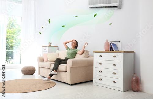 Fototapeta Happy young woman switching on air conditioner with remote control at home obraz