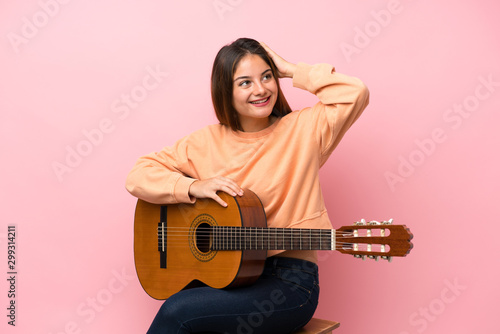 Young brunette girl with guitar over isolated pink background has realized something and intending the solution - 299314211