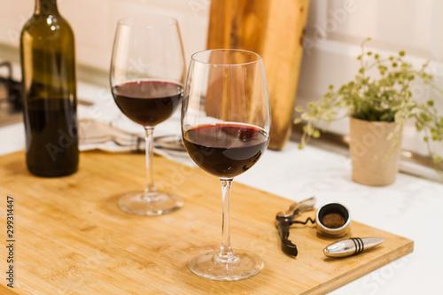 Photo Copas de vino tinto sobre tabla de madera rústica en la cocina vista de frente