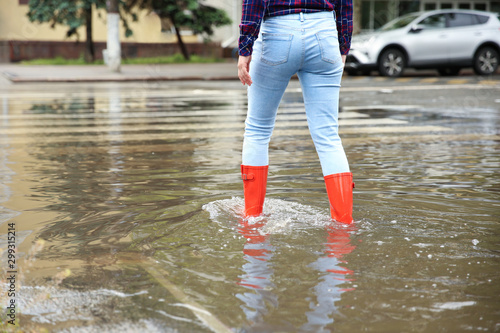 Fotobehang Londen Woman with red rubber boots in puddle, closeup. Rainy weather
