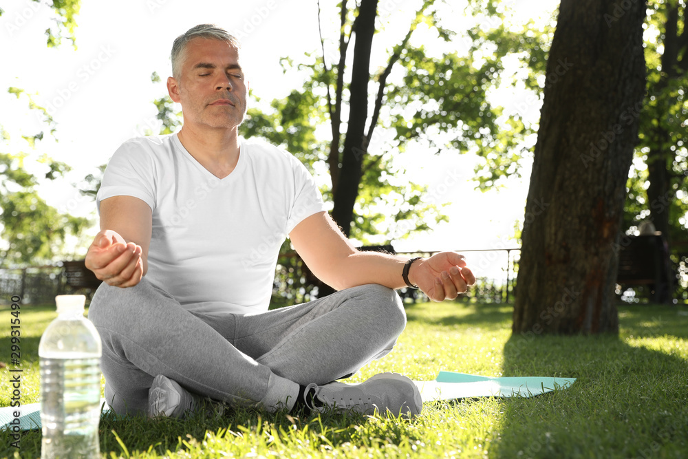 Fototapety, obrazy: Handsome mature man practicing yoga in park, space for text. Healthy lifestyle