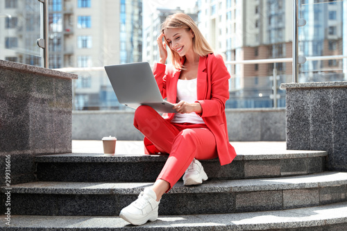 Beautiful businesswoman with laptop sitting on stairs outdoors