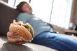 canvas print picture - Overweight boy with burger sleeping on sofa at home