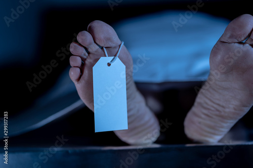 Photo Cadaver on autopsy table at morgue, label tied to toe, close-up