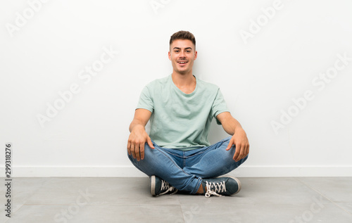Obraz Young handsome man sitting on the floor with surprise facial expression - fototapety do salonu