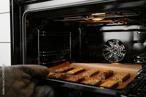 Woman taking delicious healthy granola bars from oven, closeup Canvas Print
