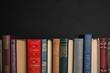 Leinwandbild Motiv Stack of hardcover books on black background. Space for text