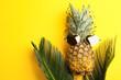Leinwandbild Motiv Pineapple with sunglasses and palm leaves on yellow background, flat lay
