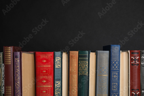 Stack of hardcover books on black background. Space for text Fototapet
