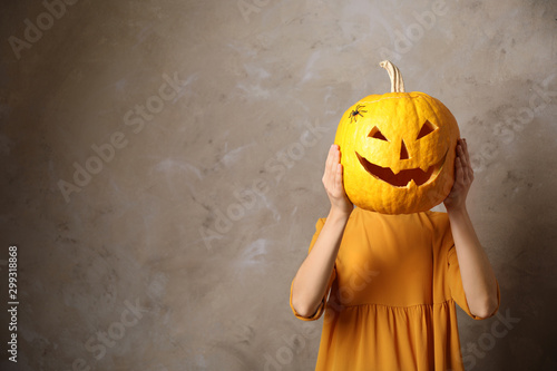 Pinturas sobre lienzo  Woman with pumpkin head against beige background, space for text