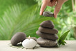 Leinwanddruck Bild - Woman stacking stones on table against blurred background, closeup. Zen concept