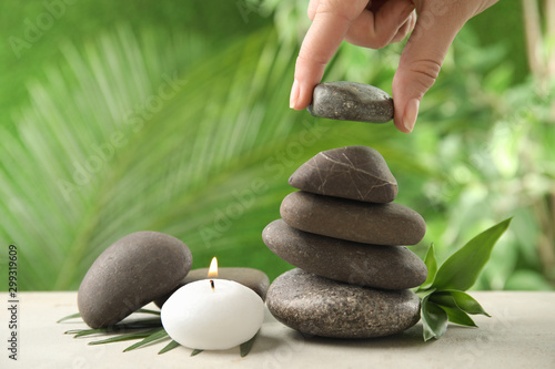 Woman stacking stones on table against blurred background, closeup. Zen concept