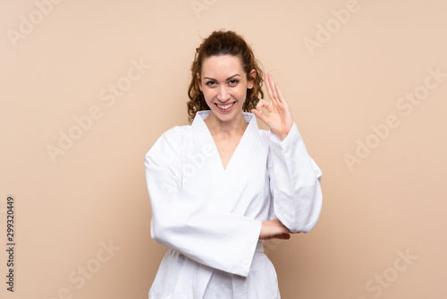 Young woman doing karate showing ok sign with fingers Wallpaper Mural