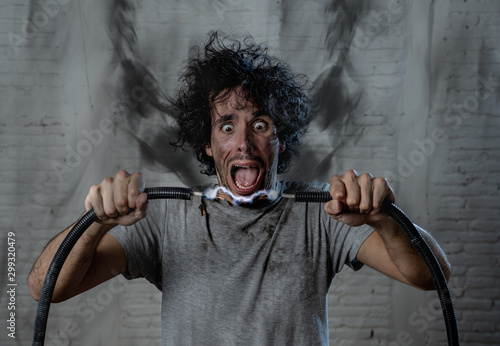 Fototapeta  Funny image of man getting electric shock with funny face and smoke all around