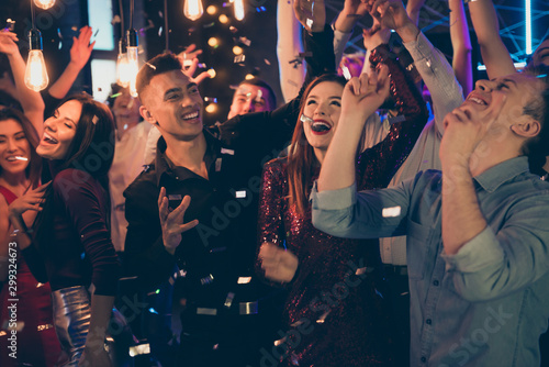 Photo of cheerful excited crazy beautiful young millennials dressed in formalwear celebrating birthday of their friend at night club having relax and fun under falling confetti