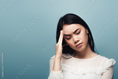 upset brunette asian woman with headache on blue background Tablou Canvas