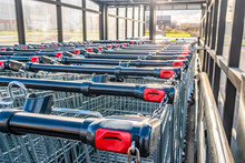 Rows Of Shopping Trolleys With Pay System. Attribute Of A Supermarket And A Supermarket In A Metropolis.