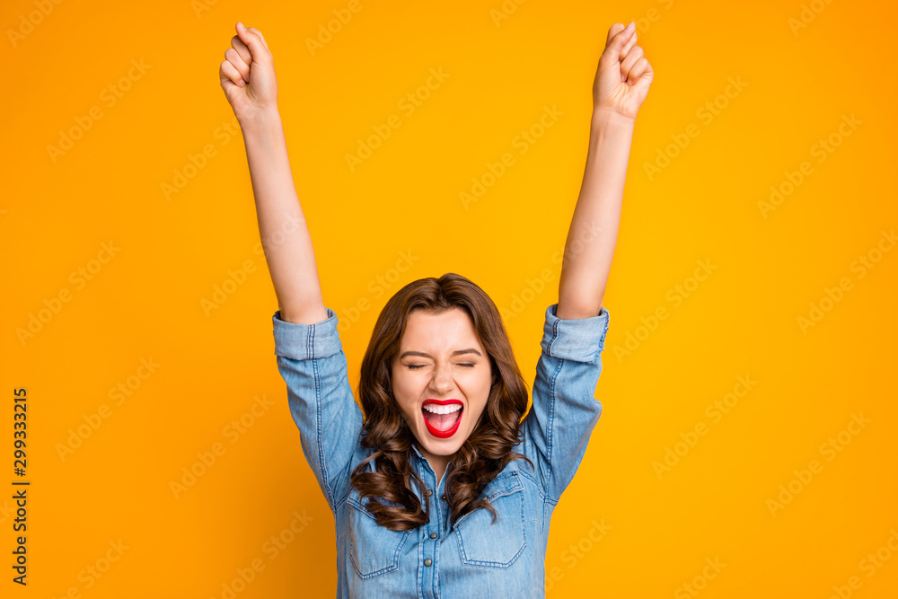 Fototapeta Photo of overjoyed rejoice girl shutting her eyes in a fit of happiness raising her hands celebrating her victory isolated over yellow vivid color background
