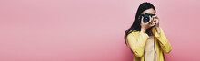 Asian Woman In Yellow Outfit Taking Picture On Digital Camera Isolated On Pink, Panoramic Shot
