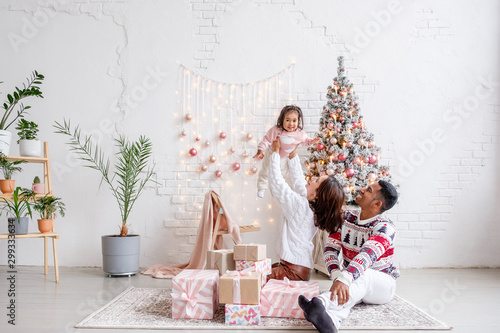 Foto  Happy mixed race family african american dad mom and daughter rejoice celebrating Christmas sitting on living room floor in beautiful bright interior with Christmas tree and decorations