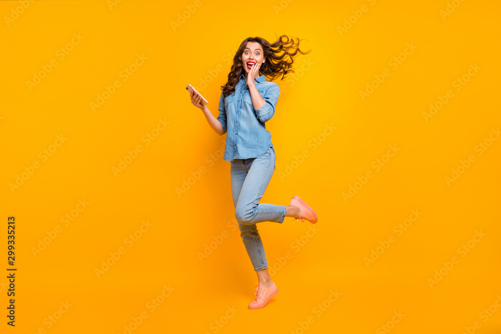 Fototapeta Full length body size photo of cheerful crazy sweet pretty girlish feminine youngster overjoyed about having received long expected message holding phone expressing emotions isolated vivid color
