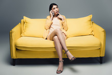 Pensive Asian Businesswoman Sitting On Yellow Sofa With Crossed Legs And Talking On Smartphone On Grey Background