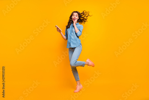 Obraz Full length body size photo of cheerful crazy sweet pretty girlish feminine youngster overjoyed about having received long expected message holding phone expressing emotions isolated vivid color - fototapety do salonu