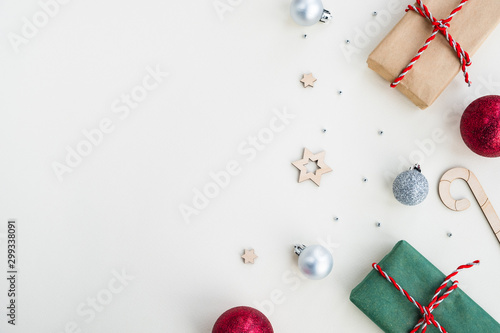 Fototapeta Christmas and New Year composition. Gift boxes and festive decor on a light beige pastel background. Top view, flat lay, copy space  obraz na płótnie