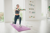 Full length photo of joyful active athlete woman holding strong dumbbells doing gymnastics exercise standing on purple mat in house like gym