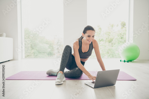 Full body photo of positive sporty girl using her computer browsing internet want find film movies video about sport fitness sit on purple mat in studio like house indoors