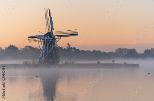 Nature awakens at a traditional Dutch windmill during a foggy sunrise. De Helper, Groningen.