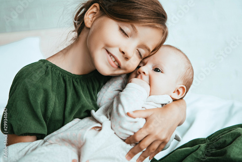 adorable child smiling with closed eyes while holding little sister Fototapet