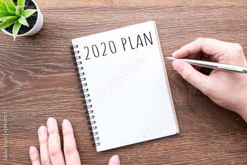 Photo  Man hand is going to write 2020 plan and goals on notebook