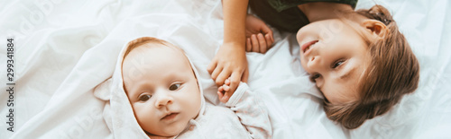 panoramic shot of smiling child holding hand of little sister lying on white bedding