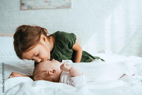 Fotografie, Obraz adorable child kissing little sister lying on white bedding