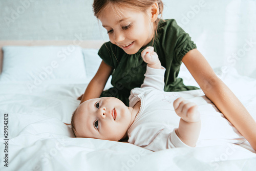 smiling child looking at adorable infant lying on white bedding Tablou Canvas