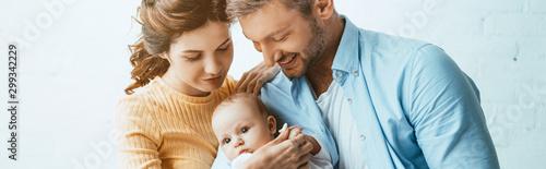 Fotografía  shot of happy parents smiling while holding little daughter together