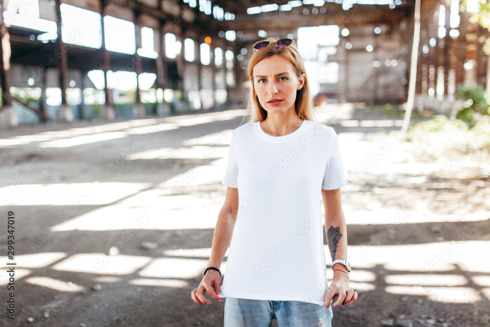 Fototapety, obrazy: Girl wearing white t-shirt, glasses and leather jacket posing against street , urban clothing style. Street photography