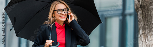 plakat panoramic shot of attractive and smiling businesswoman in black coat holding umbrella and talking on smartphone