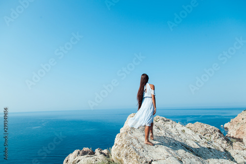 Foto auf AluDibond Blau A beautiful woman with long hair in a dress looks at the landscape