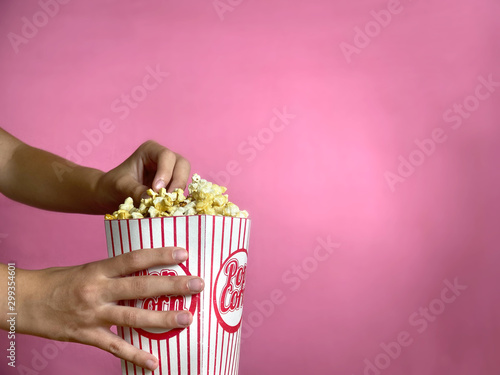 Girl is holding popcorn and eating it - 299354601